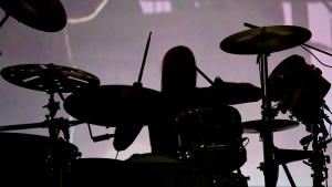 Taylor Hawkins of the Foo Fighters sits behind a drum kit (in silhouette).