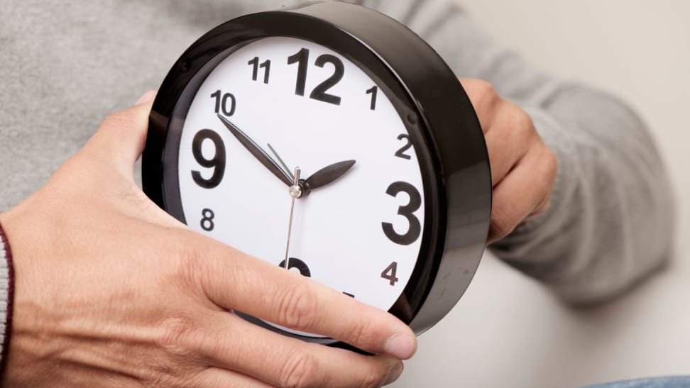 a man holds a clock and changes the time on it.