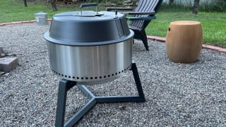 A portable charcoal grill sits on a pebble-covered yard.