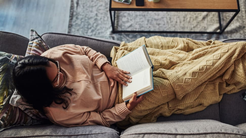 Woman spread out reading on a couch.