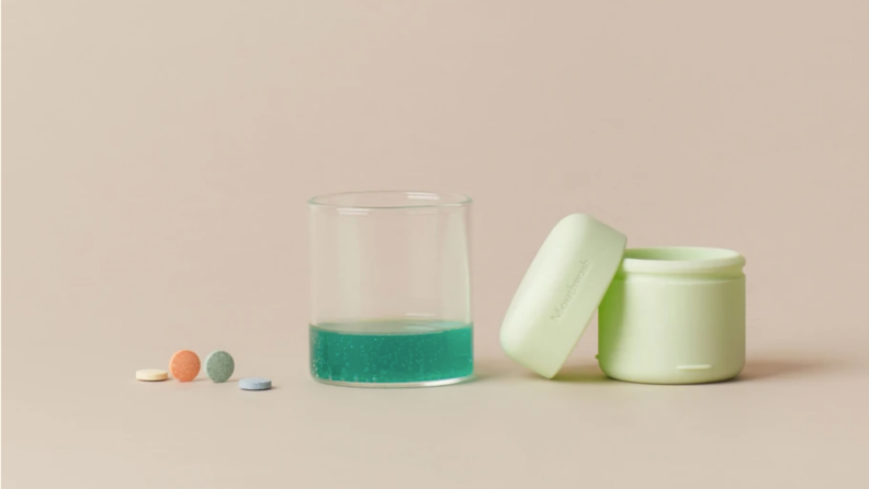 Mouthwash tablets, a carrying case, and mouthwash in a glass.