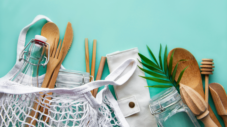 Cotton mesh bag, glass bottle, jar and bamboo cutlery on pastel green background.
