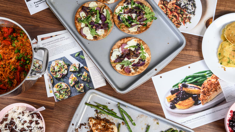 A selection of meal kit recipe cards and prepared food laid out on a table viewed from above.