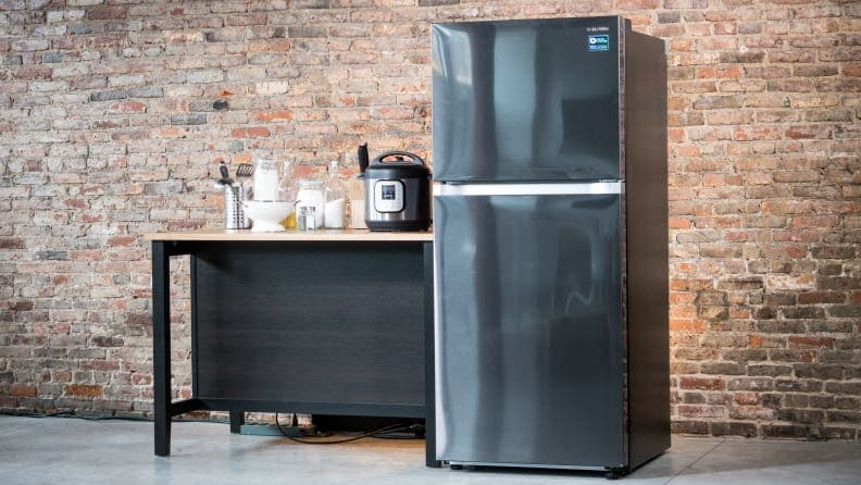 A top-freezer fridge stands in a room against a brick wall