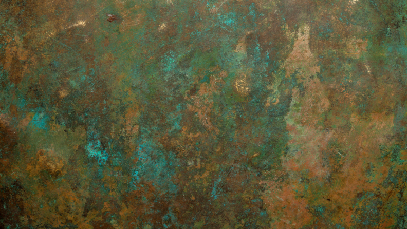 A detail of an oxidized copper vessel with shades of green and brown.