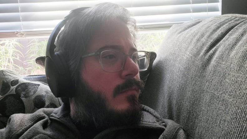 Man relaxing on a couch, wearing the Bose QC45 headphones