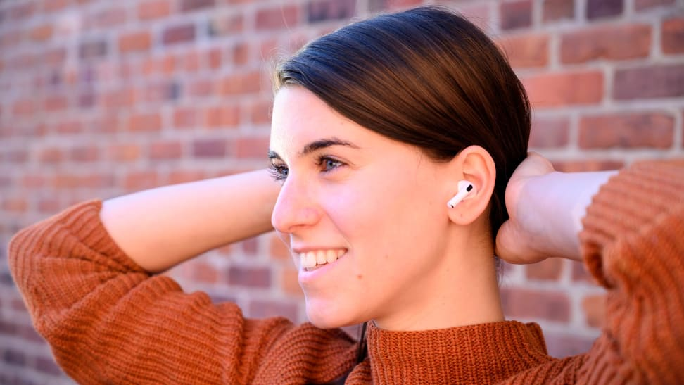 A woman wearing a pair of Apple AirPod Pro wireless earbuds.