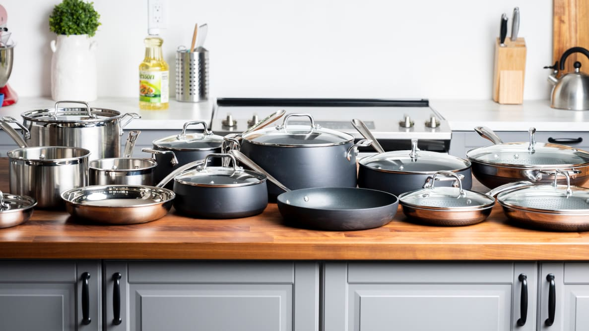 Three complete cookware sets are lined up on a kitchen island
