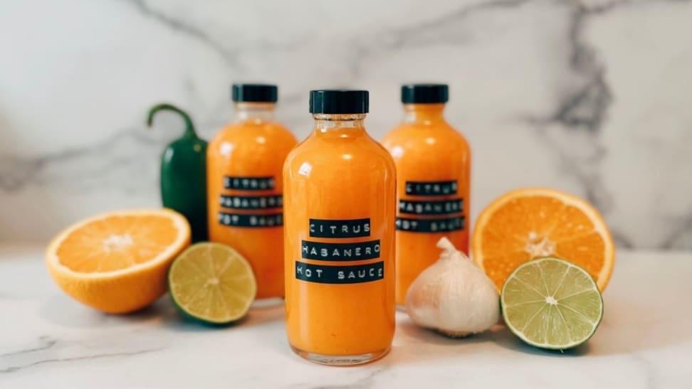 Homemade orange habanero hot sauce on a marble surface.