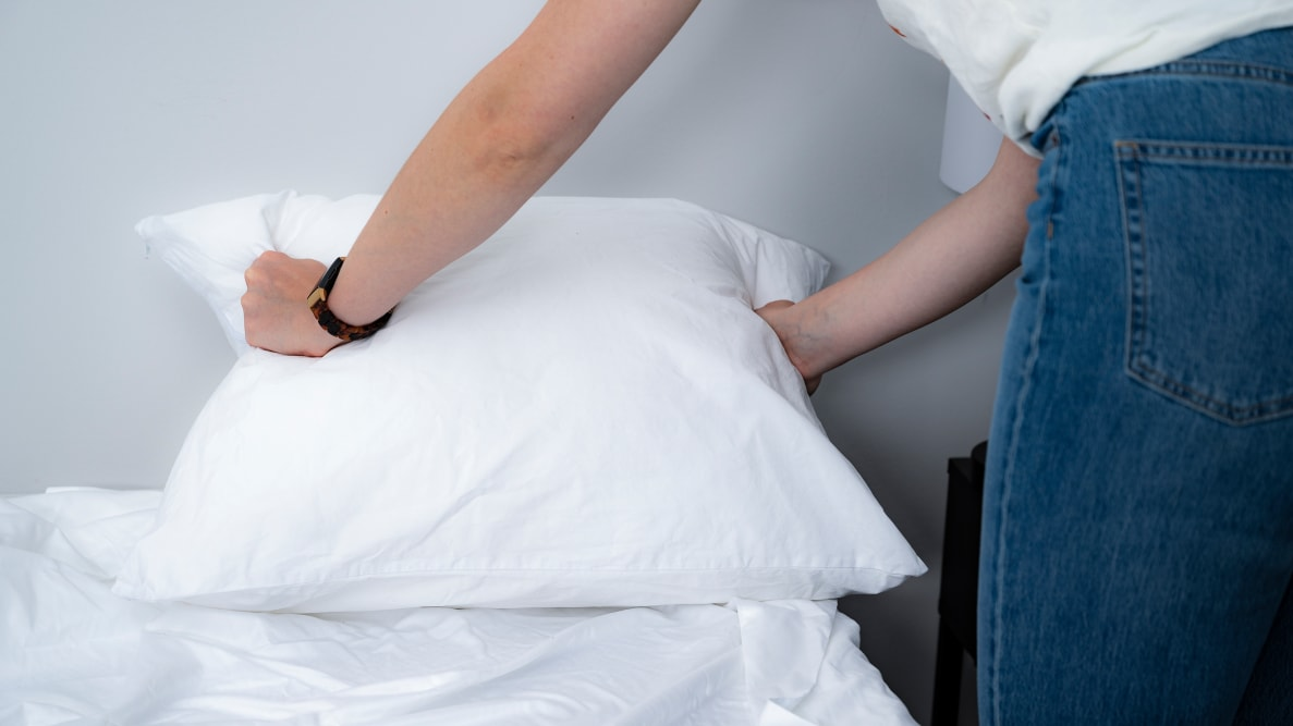 a woman holds the edges of a pillow in a pillow protector
