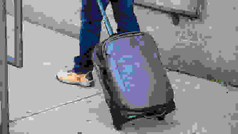 A soft-sided carry-on bag is pulled down a sidewalk, by its extendable handle