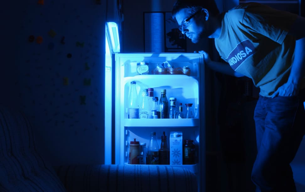 A man looking inside a refrigerator at night