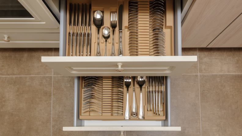 An opened kitchen drawer with silverware sets, viewed from above.
