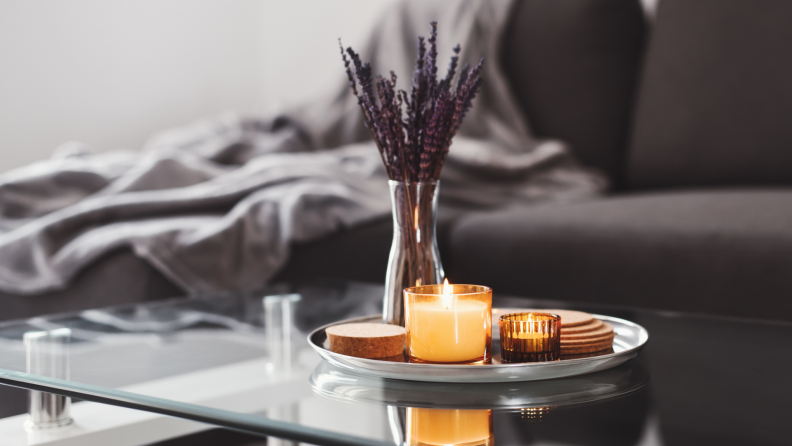 Closeup of a coffee table with a tray including a candle and lavender.