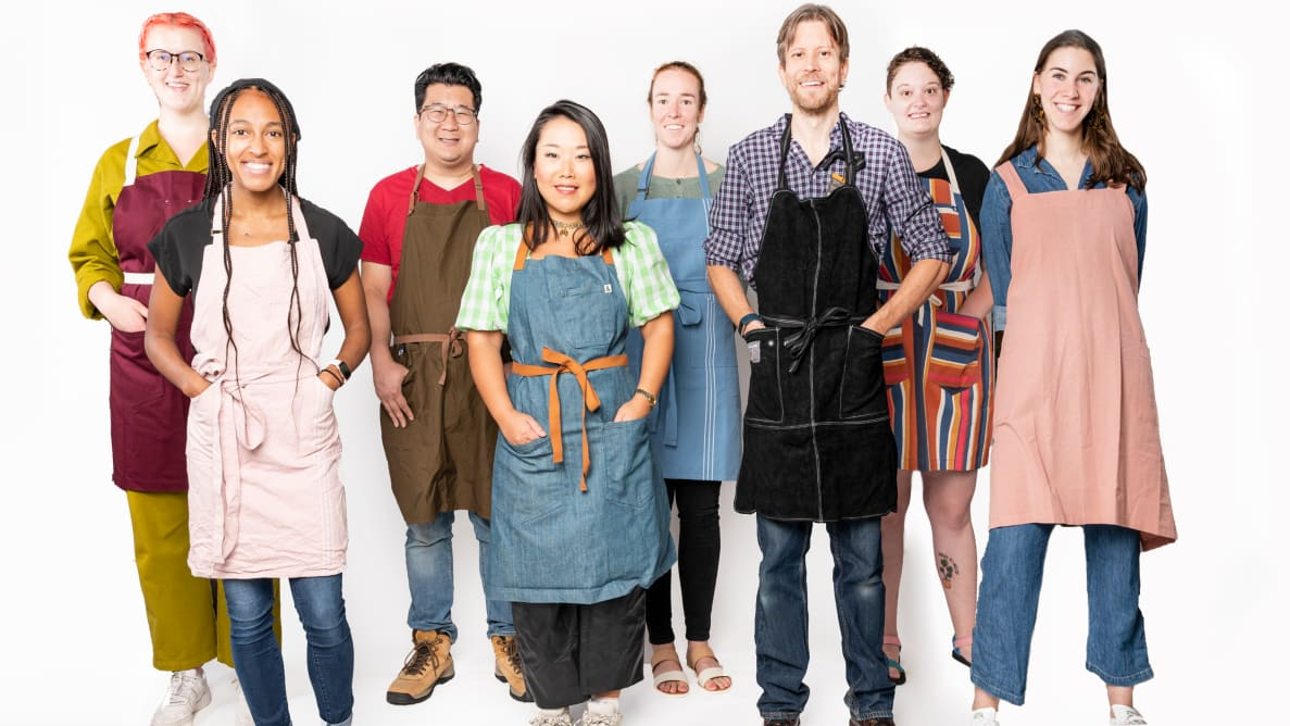 A group of people poses wearing aprons.