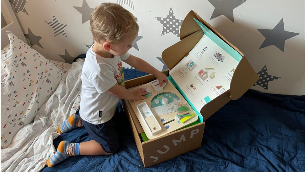 A young boy opens a cardboard box in bed