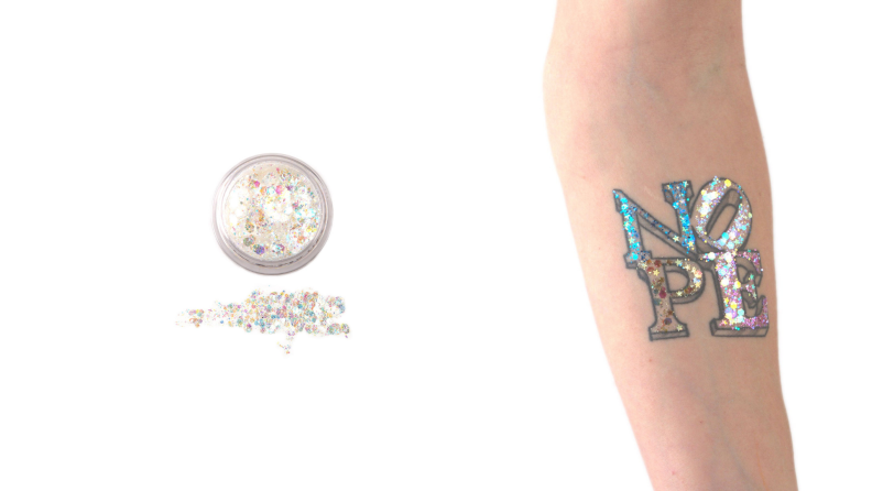 A dollop of makeup glitter added to a faux arm tattoo.