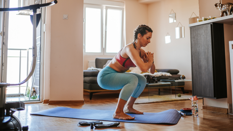 In their living room, a person performs squats on a yoga mat.