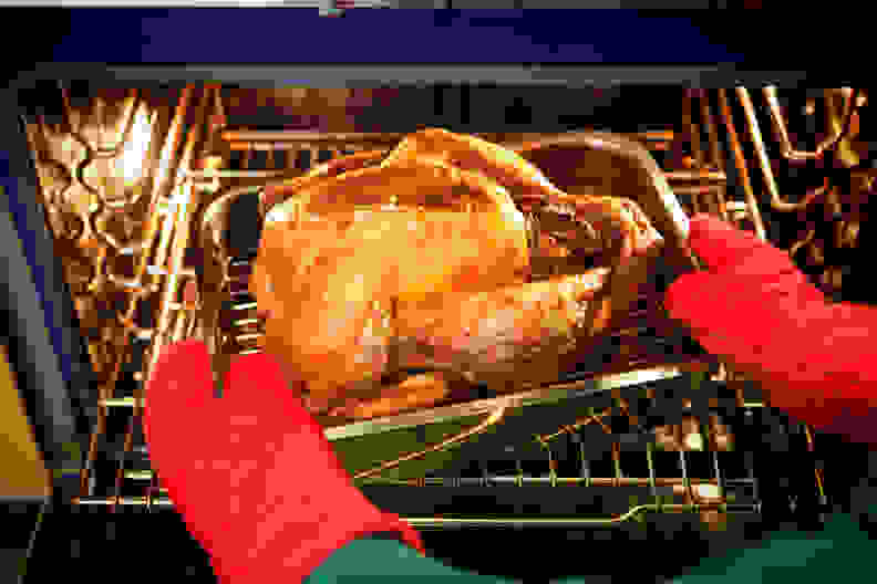 Freshly roasted turkey with stuffing coming out of the oven.