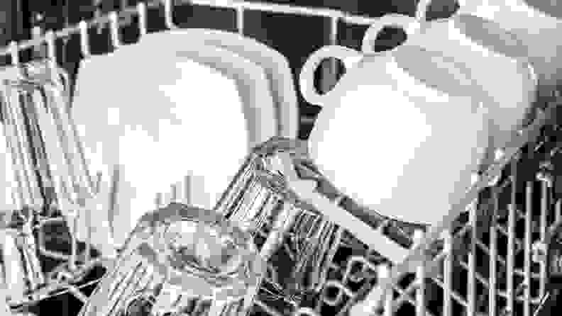 White mugs and plates and clear cups placed upside down in a dishwasher.