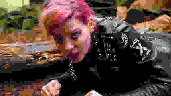 A woman with pink hair and in a black leather jacket on the ground, in a scene from