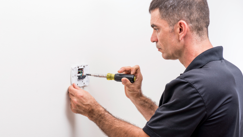 Pro installing a smart thermostat