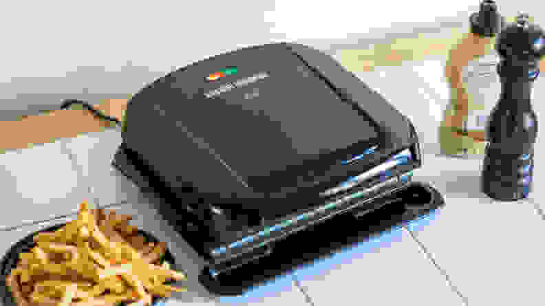 A black George Foreman 4-Serving Removable Plate Grill viewed from a front right angle.