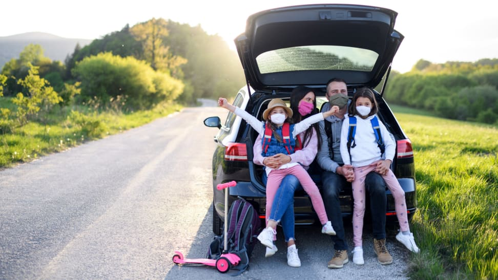 A family wears face masks during a road trip.
