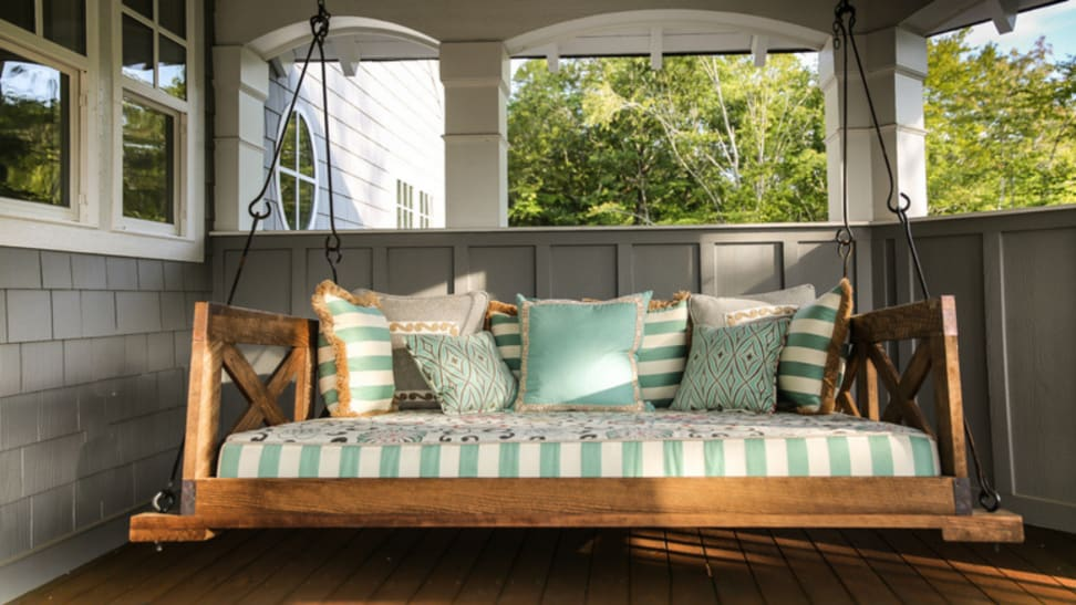Wooden porch swing with pillows on sunny front porch.