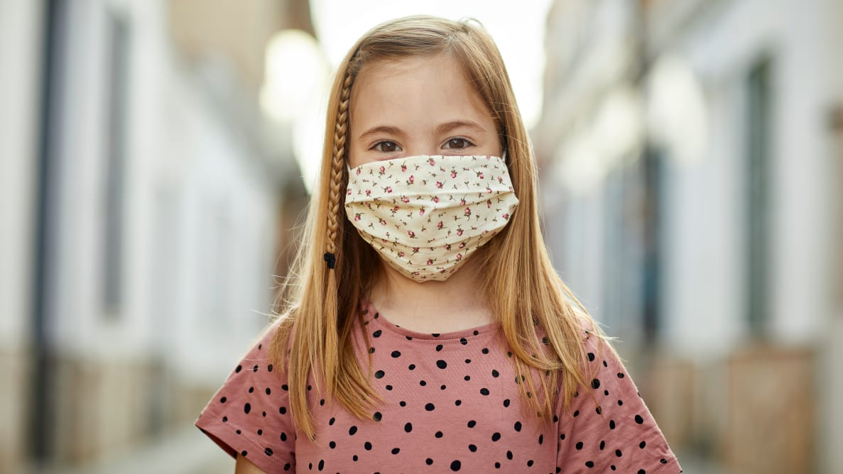 A little girl wearing a printed face mask