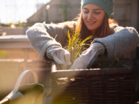Person smiling while gardening outside in the cold.