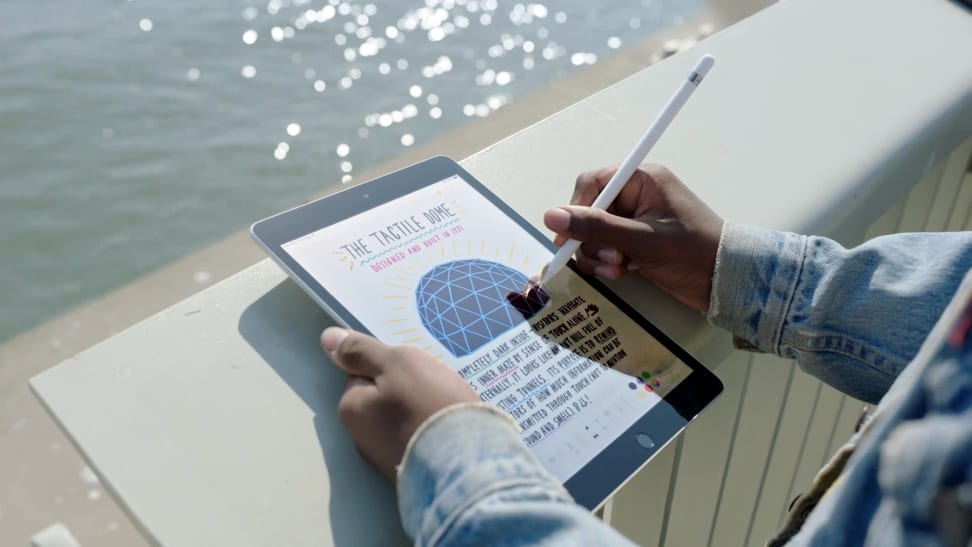A man holding an iPad and Apple Pencil in the sunlight