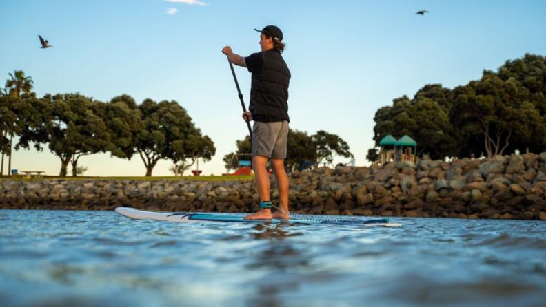 A man paddling on a board.