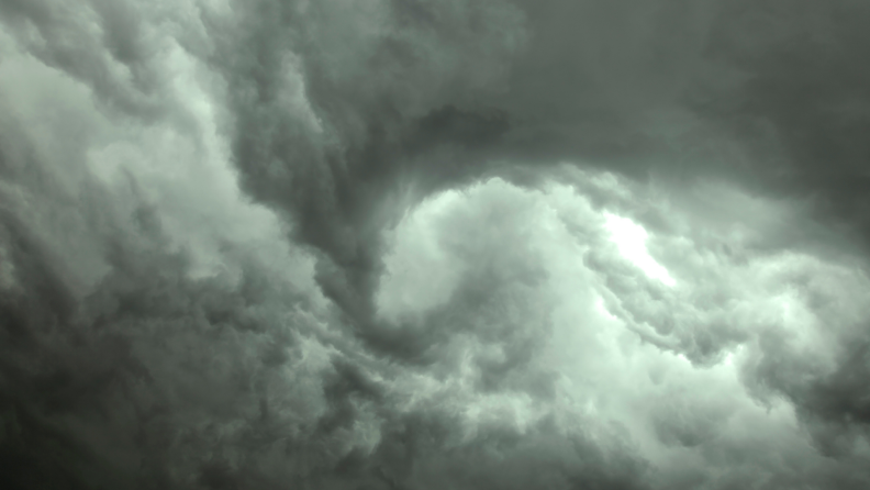 Green and gray colored storm clouds forming a funnel cloud