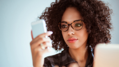 Woman with curly afro is using reading glasses to read something off of her phone.