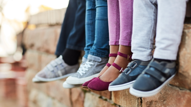 Four pairs of children's feet and legs wearing different shoes