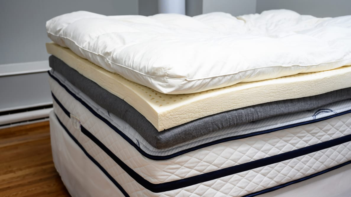 Close-up photo of a foam mattress topper and other layers of bedding.