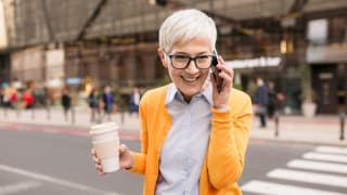 Smiling person talking on cellphone outdoors while holding cup of coffee.