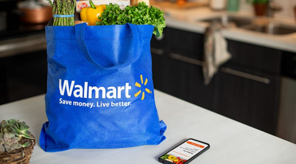 A bag of groceries sits inside of a blue Walmart bag next to a smartphone on a kitchen countertop