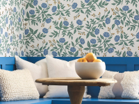 Blue wooden seating in the corner with white pillows and a blue floral decorative wallpaper from Rifle Paper Co.
