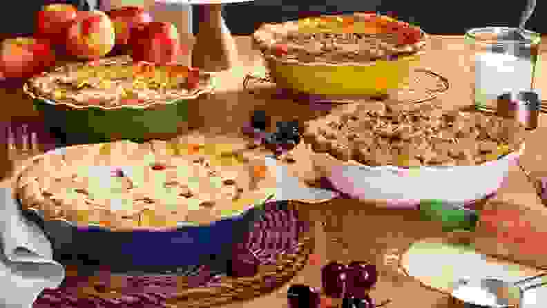 An assortment of pies sit on a dining table.