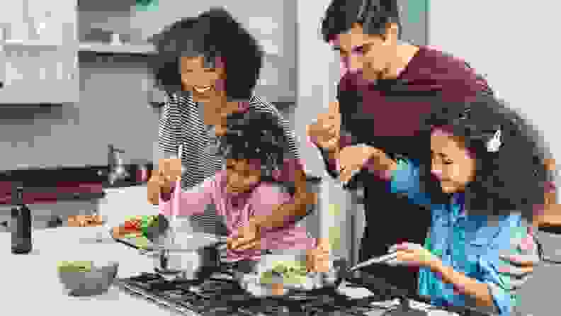 Two parents cook with the help of two children.