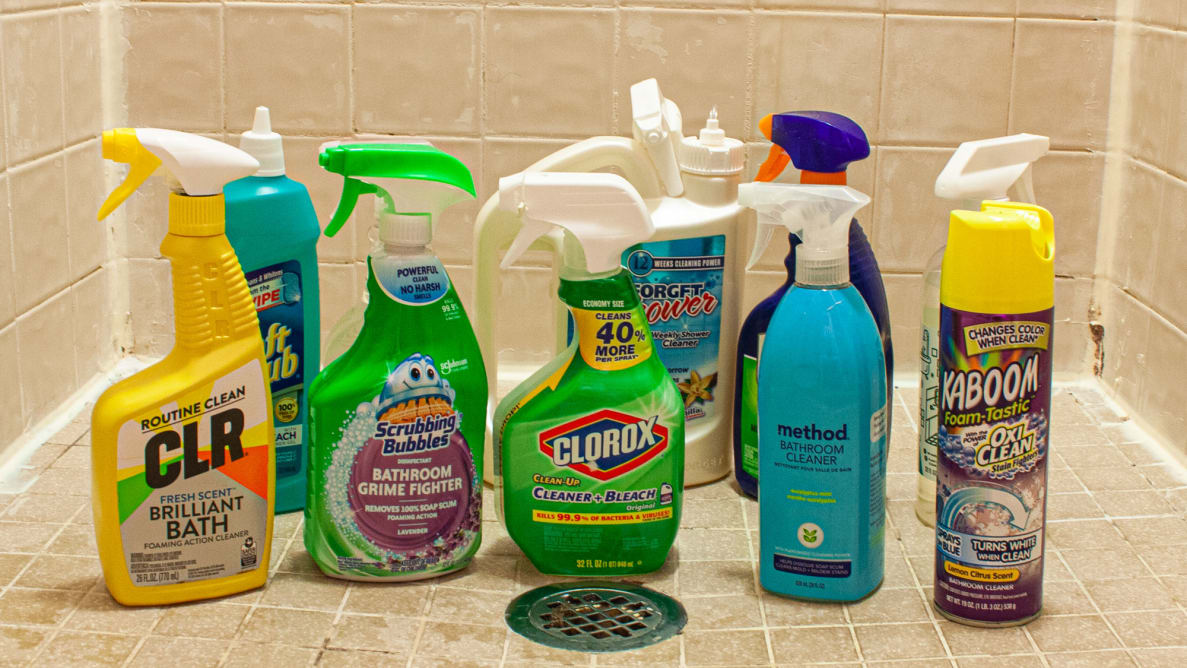 An array of shower cleaners, situated in a small shower around a drain.