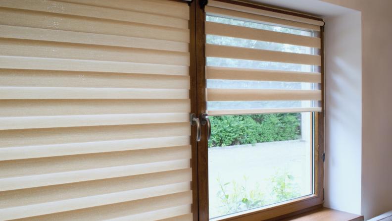 Tan window roller on a wooden window pane