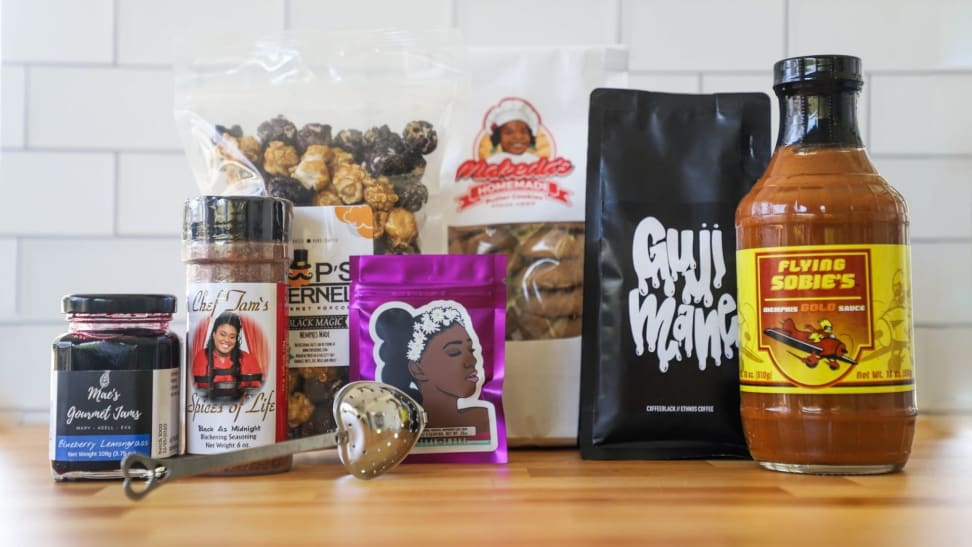 An assortment of spices and foods made by Black chefs are arranged on a light wood countertop with a white tile wall behind them.