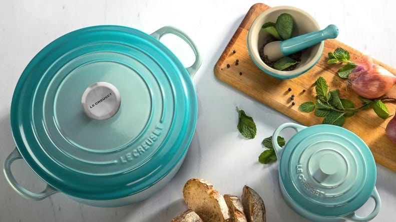 A teal Le Creuset dutch oven sitting on a countertop next to a charcuterie board.