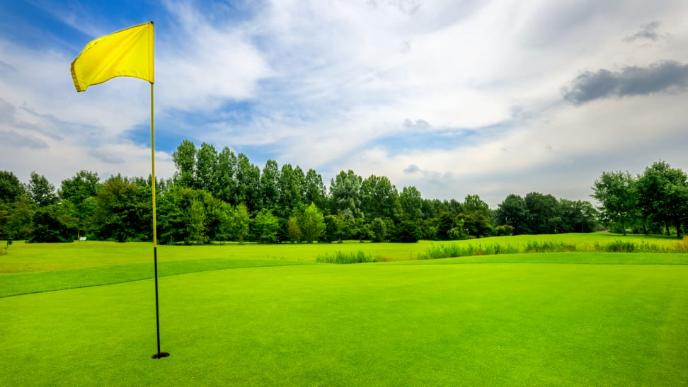 A yellow flag at the 18th hole on a golf course