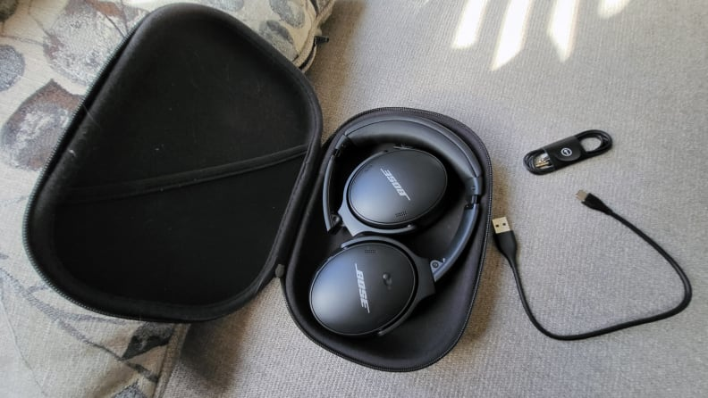 The Bose QC45 in their carry case, with USB-C and 3.5mm cable on a couch