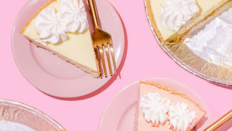 A piece of regular key lime pie and a piece of strawberry key lime pie sit on two pastel pink plates, accompanied by the half-empty aluminum pie tins against a pink background.