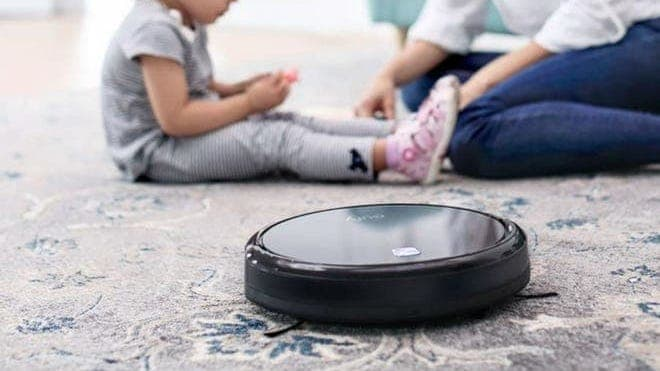A Eufy 11S robot vacuum cleaning a carpet with a woman and child sitting in the background.